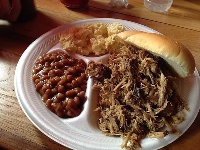 "The Bar-B-Q Place is located in Fayetteville! They proudly serve ""good ol' hickory smoked Bar-B-que!"" With very reasonably priced barbeque, if you're in the area, it is a must try! Pictured here is their very popular dish, the Pulled Pork sandwich."