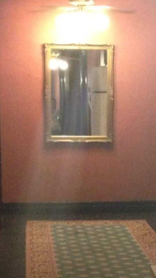 """Here's what our viewer had to say about this picture:""""I still have a hard time believing this one myself – but there was no on in that hallway except for me and my husband and that's not either one of us. Our tour group was nearby but they weren't in the hall… I've wondered if it was a reflection off of another mirror or something but I've looked through all of our pics and no one in our group was wearing a white shirt like this one. Freaky!"""""""