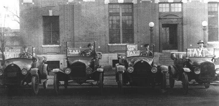 Taxi Model T cars lined up in front of the old Fayetteville post office.