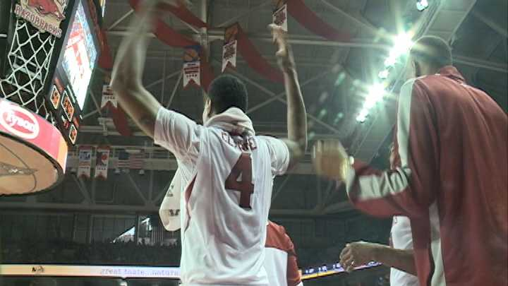 Arkansas forward Coty Clarke helps pump up the Bud Walton Arena crowd from the sidelines.