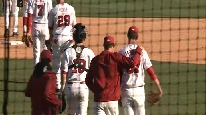 Chris Falwell is congratulated at the mound by Trey Killian after closing out a Razorback win.