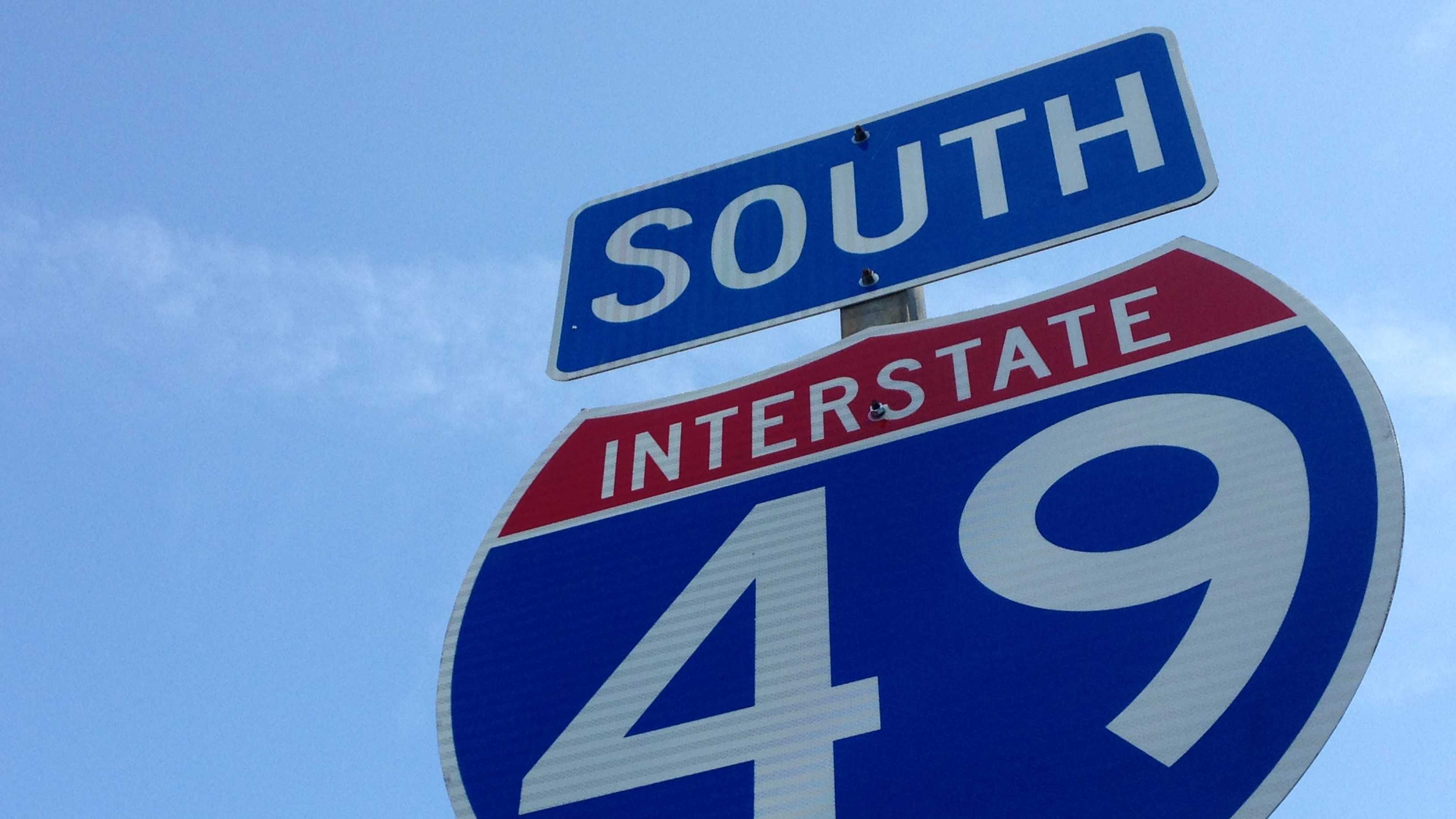 Crews place Interstate 49 signs along roadway during rush-hour commute
