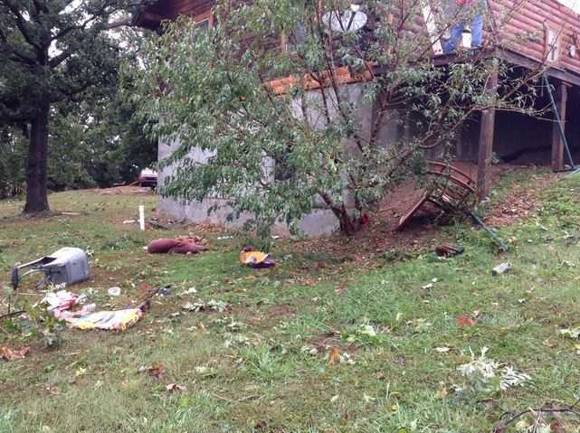 Homeowner says this debris, including rocking chair on right, was swept from the front porch to the back of the house