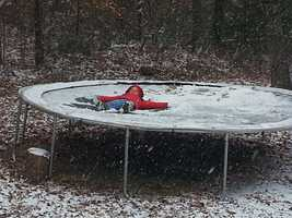 Jayden making snow angels on the trampoline in Hindsville