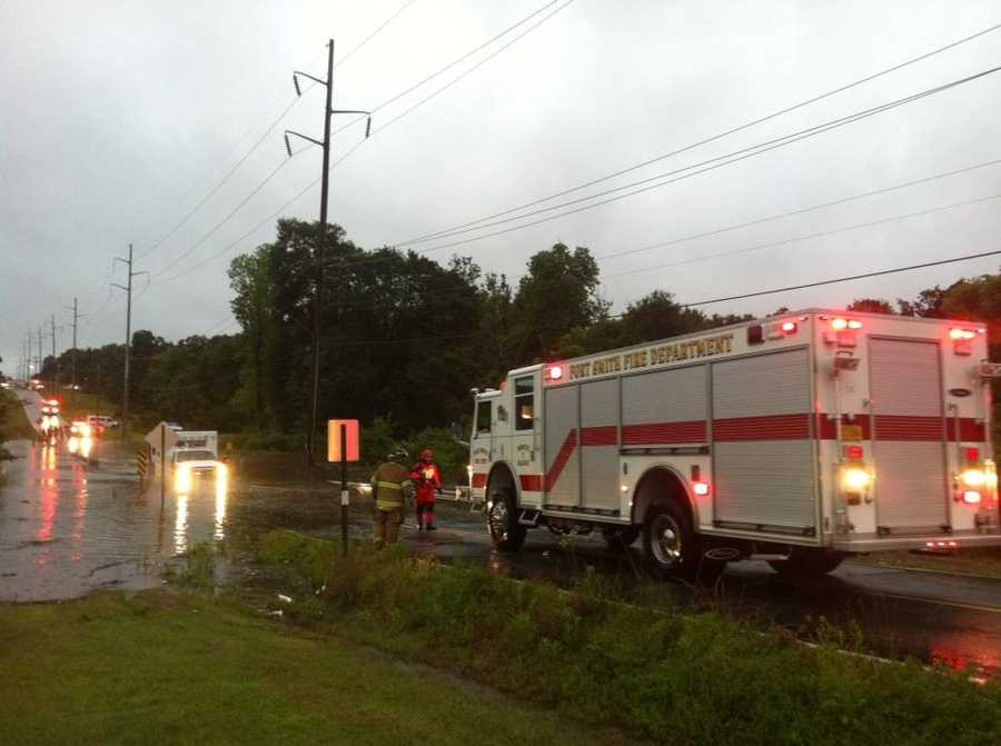 A fire truck works to pull an ambulance out of a flooded roadway that got stuck.