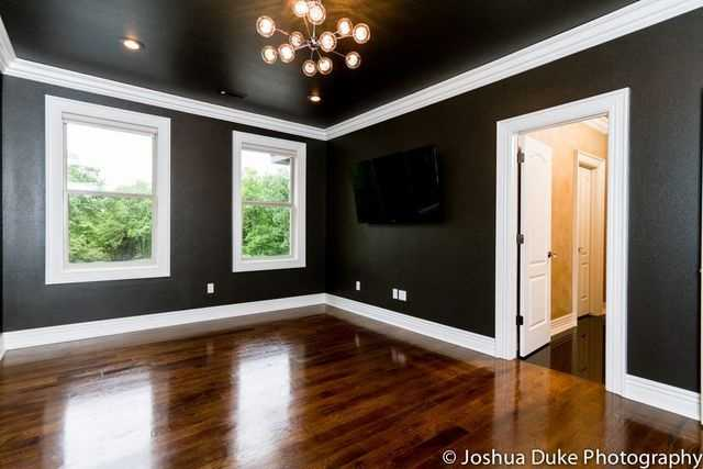 This is a beautiful living space with polished hardwood floors and a modern lighting fixture.