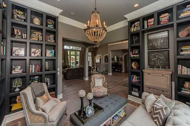 This library is simply breathtaking with its in-wall shelving, chandelier, and comfortable seating.