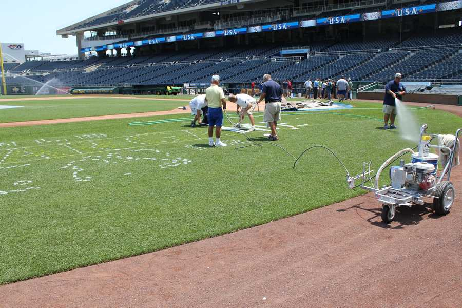 Crews paint the All-Star logo on the field at the K while others water it to keep it green.