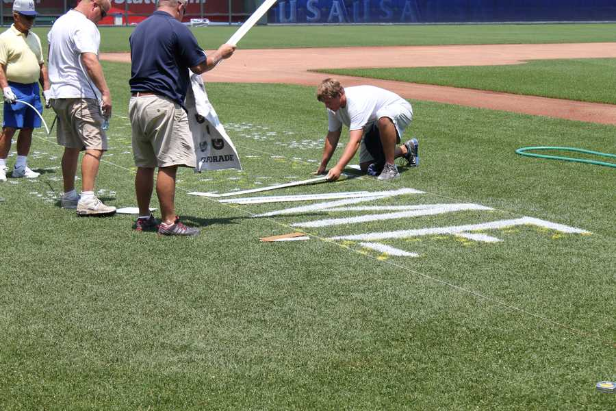 Crews using a stencil to put the All-Star logo on the field along the third base line.