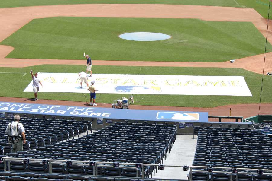 A closer view of the All-Star Game logo getting painted onto the field along the third base line.