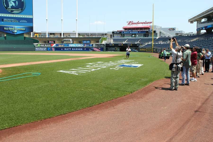 Members of the media watch as the All-Star logo is painted along the first base line.