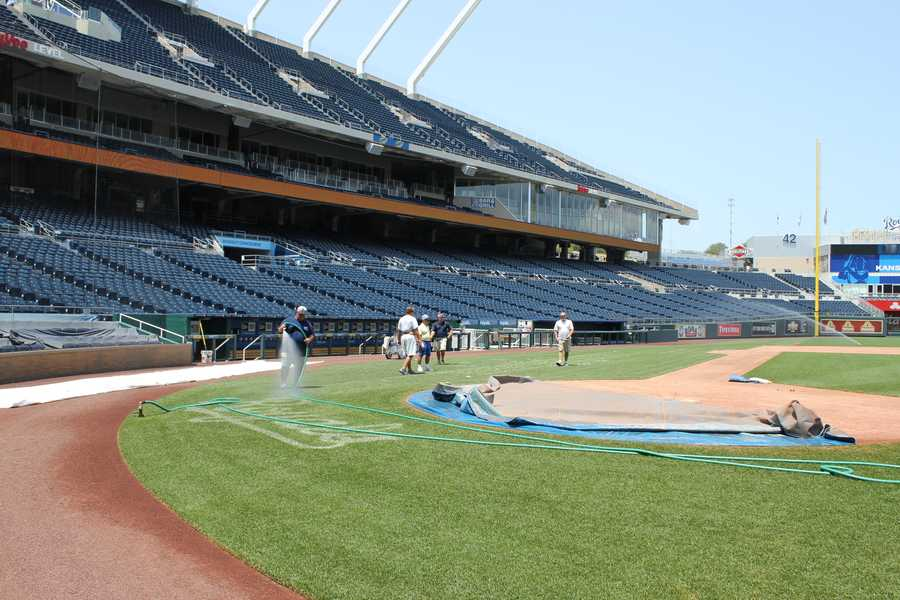 Ground crews are painting All-Star logos on to the field at Kauffman Stadium.