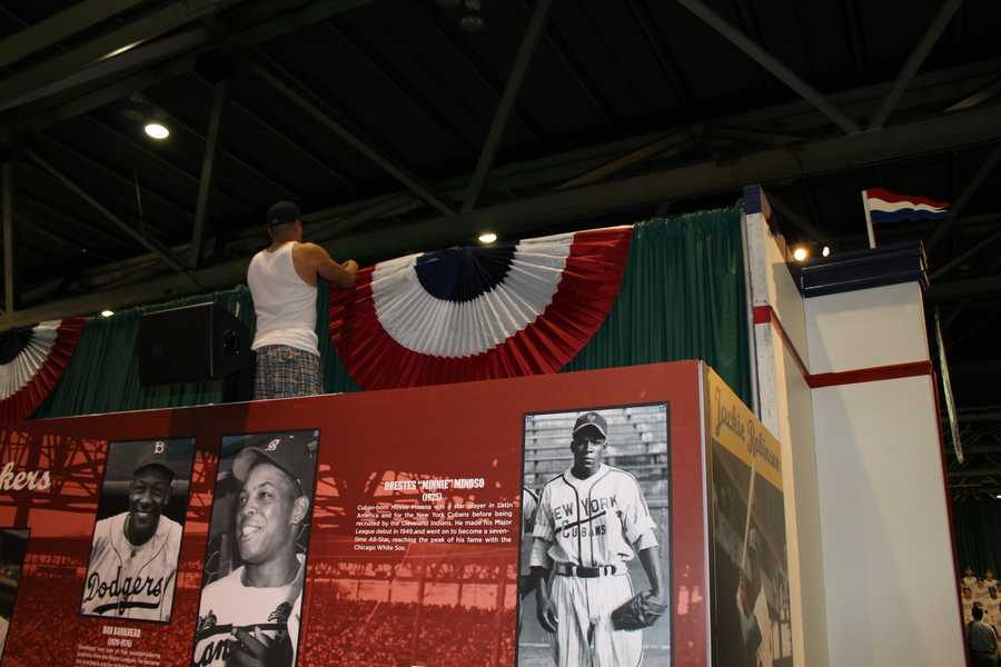 A worker puts up some bunting inside the Negro Leagues display.
