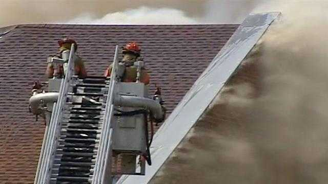 Firefighters battle the fire from a ladder truck.