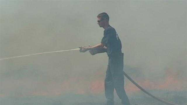 Firefighters rushed to put out a grass and hay fire that may have spared a neighborhood by winds that kept the flames away. KMBC 9's Haley Harrison reports.