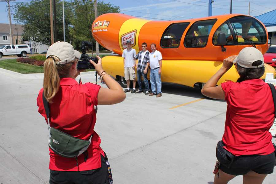 People getting their pictures taken with the Wienermobile.