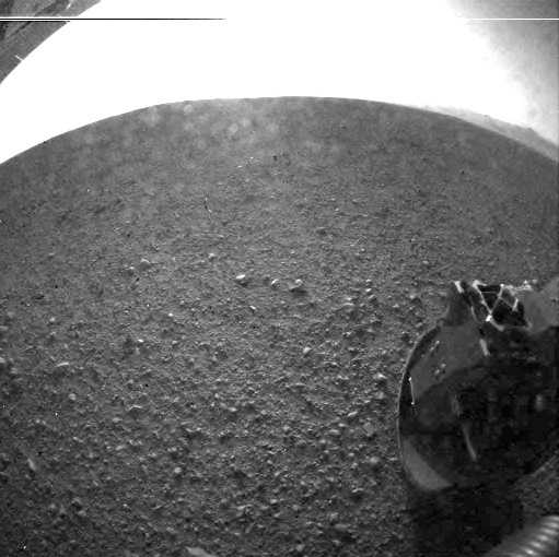 "From NASA.gov: This is one of the first images taken by NASA's Curiosity rover, which landed on Mars the evening of Aug. 5 PDT (morning of Aug. 6 EDT). It was taken through a ""fisheye"" wide-angle lens on the left ""eye"" of a stereo pair of Hazard-Avoidance cameras on the left-rear side of the rover. The image is one-half of full resolution. The clear dust cover that protected the camera during landing has been sprung open. Part of the spring that released the dust cover can be seen at the bottom right, near the rover's wheel."