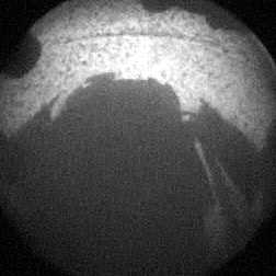 From NASA.gov:The clear dust cover on the camera is still on in this view, and dust can be seen around its edge, along with three cover fasteners. The rover's shadow is visible in the foreground.As planned, the rover's early engineering images are lower resolution. Larger color images are expected later in the week when the rover's mast, carrying high-resolution cameras, is deployed.