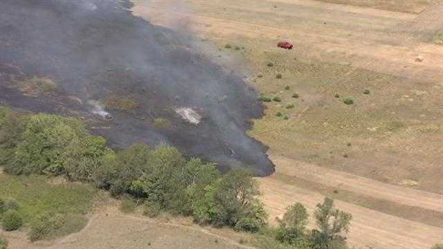 A large grass fire burns near 183rd Street and Lone Elm Road in Spring Hill, Kan., on Wednesday morning.