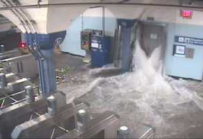 Flood waters rush in to the Hoboken PATH station through an elevator shaft.