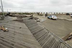 Pedestrians asses the damage from flooding near Rockaway Beach in the New York City borough of Queens Tuesday, Oct. 30, 2012, in New York.