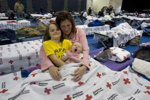 Candice Haugland of Seaside Heights, N.J., and her niece, eight-year-old Amy Hoopingarner and two-month-oldNora Remington, are settling in at the Red Cross shelter in the Pine Belt Arena in Toms River, N.J. A steady flow ofevacuees has been filling the shelter since Sunday&#x3B; shelter capacity is 1,100.