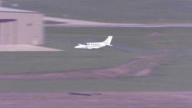 The pilot of a twin-engine plane makes a belly landing at New Century Air Center in Gardner, Kan.