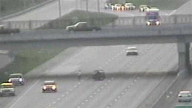 After a doghouse was blocking a lane of Interstate 70 late Wednesday, a man ran into the busy highway to push it out of the way.