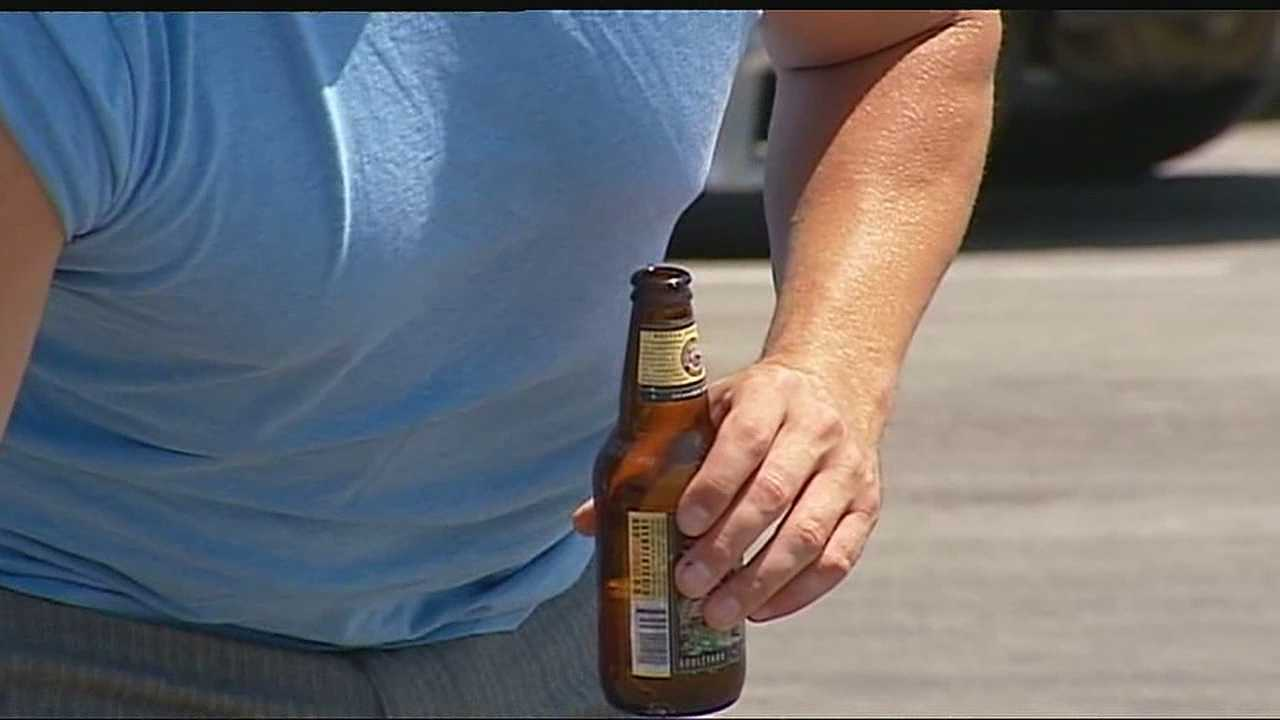 Image Hand holds beer bottle
