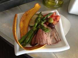 Premium guests upstairs are treated to roasted top round sirloin with asparagus, plantain chips, and a chimichurri sauce.
