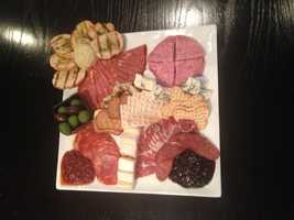 An assortment of three different cheeses, assorted meats and sausages from the Local Pig Charcuterie (Scimeca's), house made seasonal jams, pesto-brushed grilled baguette artichoke truffle purée and European olives.
