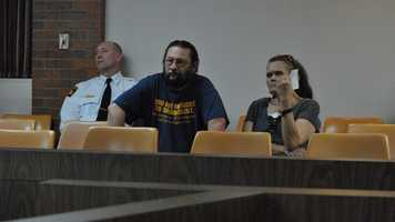 Michael and Tammy McCoy, step-father and mother of Kyle T. Flack, 28, Ottawa, who is charged in connection with the killing of three adults and an 18-month-old girl in spring 2013, listen to testimony Monday afternoon in Franklin County District Court, Ottawa, as Franklin County Sheriff Jeff Richards looks on.