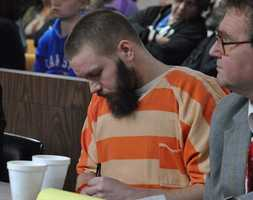 Kyle T. Flack, 28, Ottawa, who is charged in connection with the killing of three adults and an 18-month-old girl in spring 2013, takes notes Wednsday morning as Judge Thomas Sachse discusses his ruling in Franklin County District Court, Ottawa. Flack was bound over for trial on charges of capital murder, two counts of first-degree murder, and criminal possession of a firearm. An attempted rape charge was dismissed Wednesday.