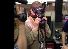 FBI agents show Peggy Breit how breathing masks are often used at crime scenes, especially when investigators enter an unknown situation.  One agent told Breit that new FBI recruits have to quickly get over any claustrophobic tendencies.