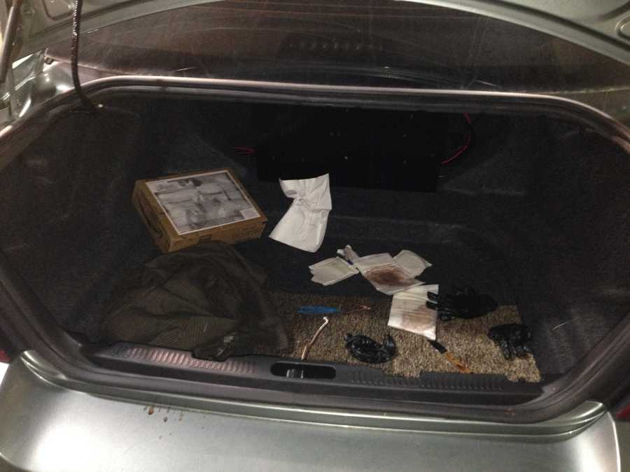 Agents open the trunk of a case to show examples of evidence.