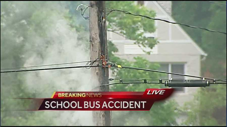 Images from the scene of a school bus rollover crash at Raytown Road and Blue Ridge Cutoff.  The bus crashed and a nearby power pole is smoking and sparking.