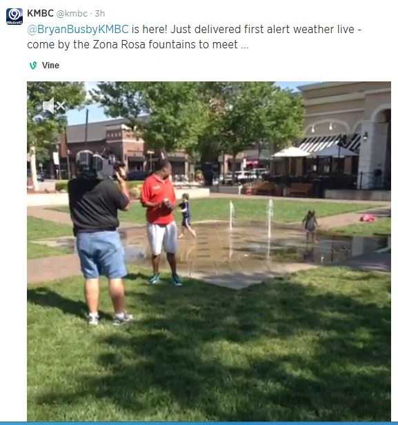 A child in the background plays with the fountains at Zona Rosa, unaware of the live TV report going on in front of him.