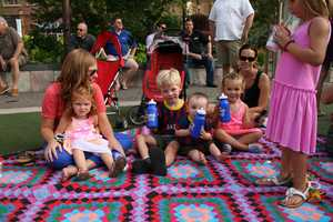 Families begin filing in and finding a comfortable picnic spot for the concert at Park Place Leawood.
