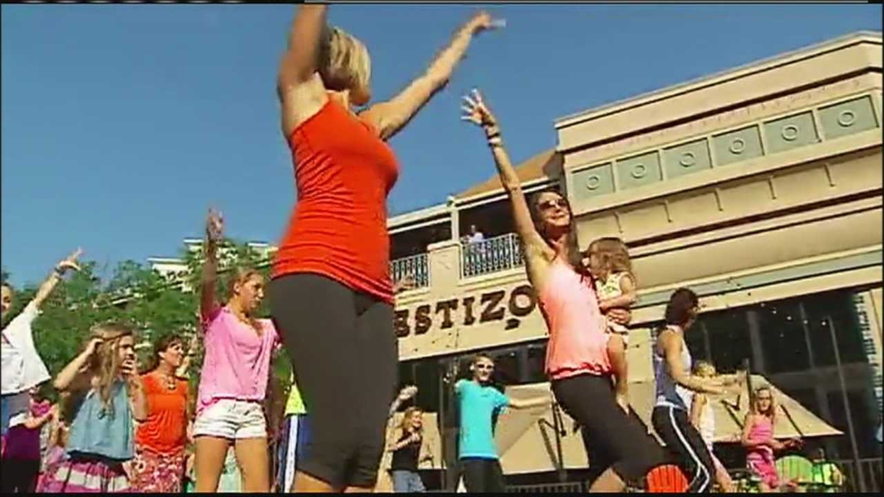 The clients and friends of a Kansas City-area fitness studio put together a flash mob Thursday to help rally around the owner as she fights cancer.