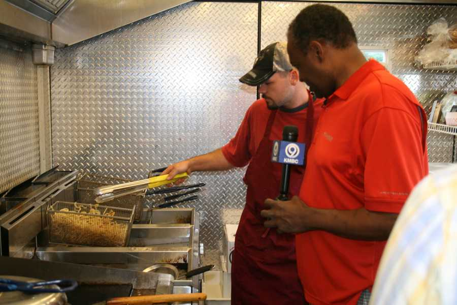 "Bryan Busby checks out the french fries inside ""Fourward Enterprises,"" owned and operated by Darrell LaClair and Brett Williams at the Cass County Fair.  This is one stop on KMBC's ""Hometown Weather"" tour."