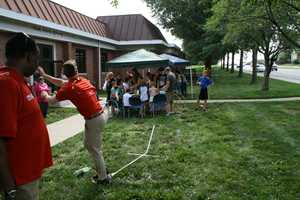"Meteorologist Nick Bender tests out the foam rocket launcher created by kids at the Oak Park Library during KMBC's ""Hometown Weather"" tour."