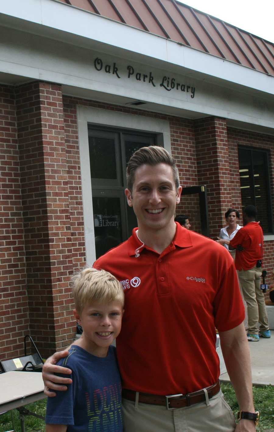 "Nick Bender takes a photo with a future meteorologist at the Oak Park Library during KMBC's ""Hometown Weather"" tour.  This event is one of many MakerSpace trips organized by the Johnson County Library system."