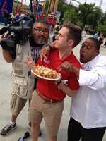 "KMBC's ""Hometown Weather"" tour traveled to Worlds of Fun Thursday.  Executive Chef Kevin Williams (right) made a funnel cake for meteorologist Nick Bender (center) and the KMBC 9 News crew.  Photographer Laz Abalos (left) was able to sample a piece."