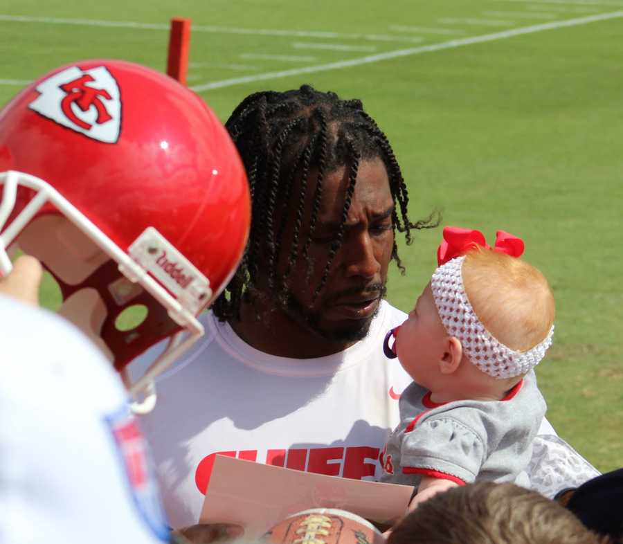 Chiefs wide receiver Dwayne Bowe holds a baby girl while signing autographs for fans after practice.
