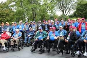 Heartland Honor Flight veterans visit the Korean War Memorial.  Veterans from multiple wars take a group photo.