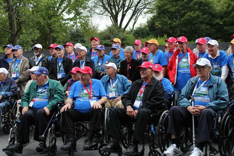 Heartland Honor Flight veterans visit the Korean War Memorial. Veterans from multiple wars take a group photo.