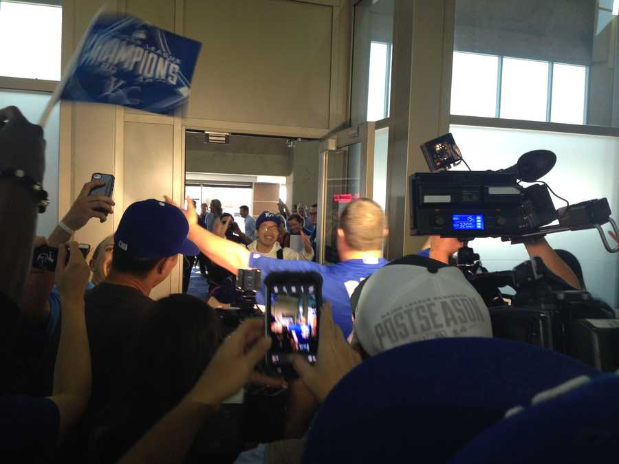 Kansas City Royals super fan Sung Woo Lee is greeted by a large crowd at Kansas City International Airport on Tuesday.