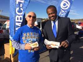 KMBC Chief Meteorologist Bryan Busby shares a hot dog with a Royals fan. The KMBC team set up shop at in parking lot A-4.