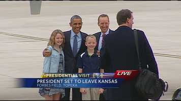 President Obama poses with a family at Forbes Field in Topeka, Kansas, just before departing on Air Force One.
