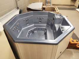 Bidding for the slate blue Sunbelt Carona Spa with whitewash cabinets starts at $2,000. The spa seats up to 8 people.